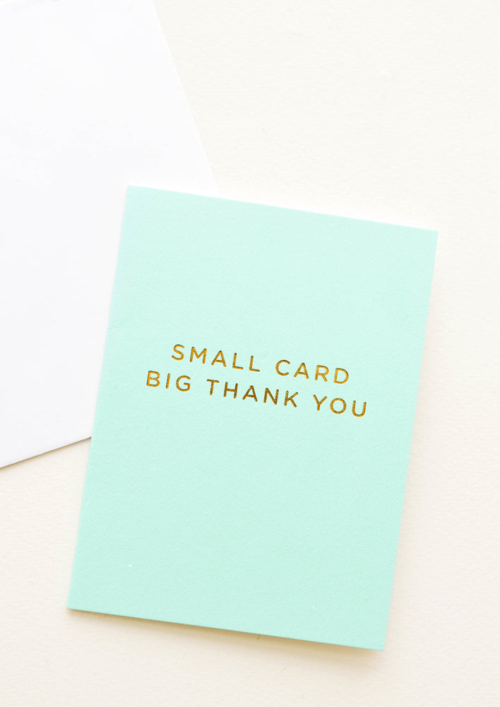 "1: An aqua colored greeting card with gold foil text reading ""small card big thank you."""