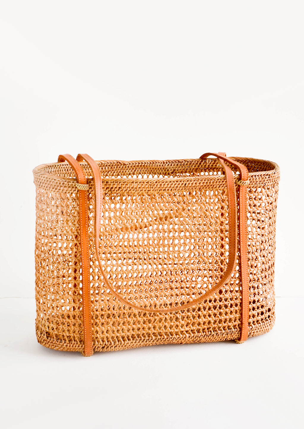 1: East-west tote bag made from open weave rattan, thin, tanned leather shoulder straps wrap around the bottom of the bag