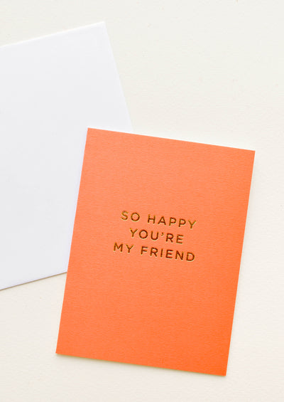 "A white envelope and orange greeting card with the words ""so happy you're my friend"" in gold foil."