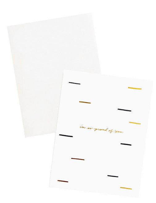 "3: A white envelope and a white greeting card patterned with short lines of black and gold and the words ""i'm so proud of you"" in gold foil."