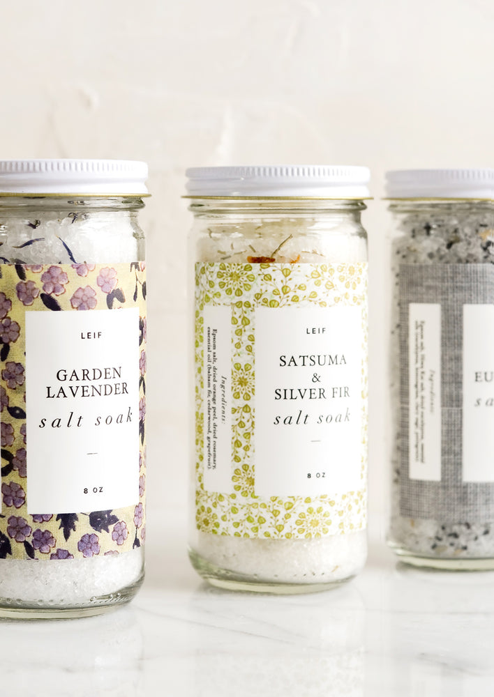 5: Three glass jars with decorative labels containing bath salt soaks.
