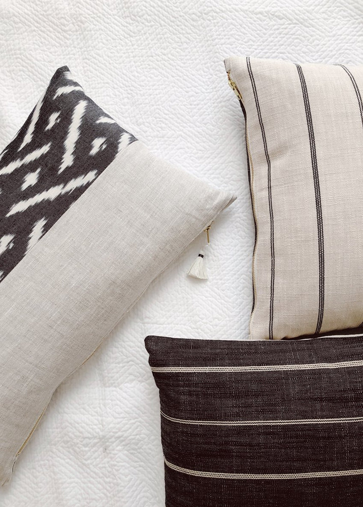 4: Black & White Pillows Casually Arranged on Bedsheets