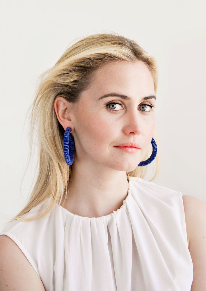 2: Model wears blue beaded hoop earrings and white blouse.