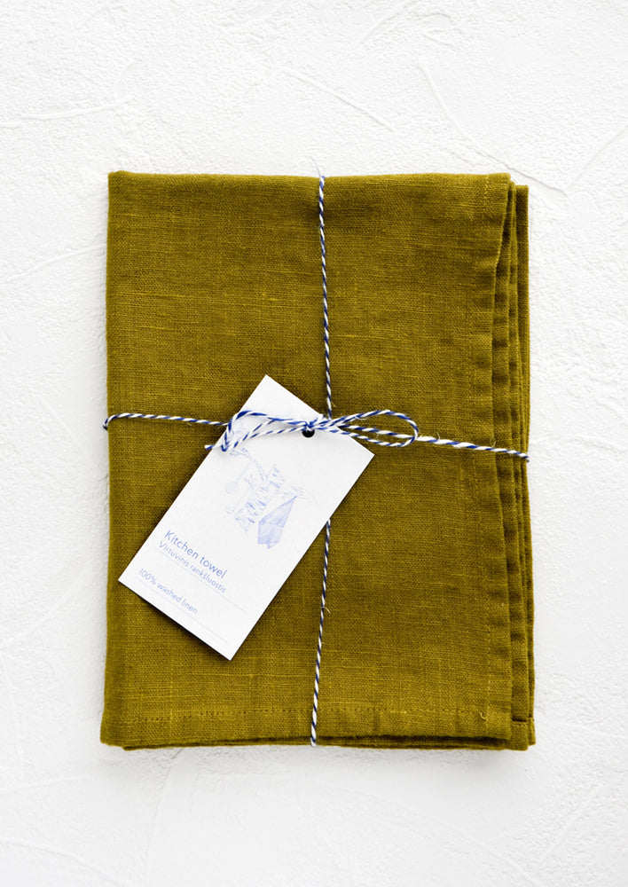 Lichen: A folded green linen tea towel tied in baker's twine with a decorative hangtag.