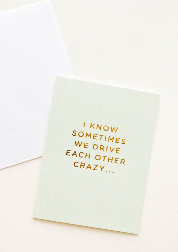 "A pale green greeting card with script reading ""I know sometimes we drive each other crazy"" in gold foil."