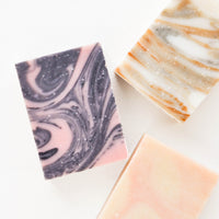 2: Three marbled bar soaps in black and pink, pink and beige, and white and orange.