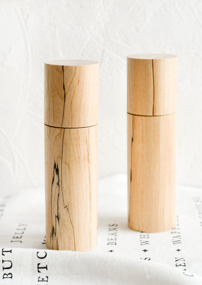 Two cylindrical pepper grinder mills in spalted maple wood.