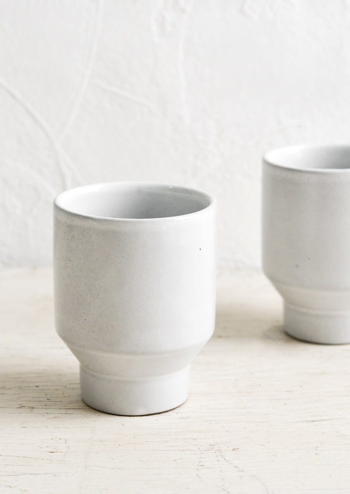 1: Glossy white ceramic cups with geo tapered bottom.