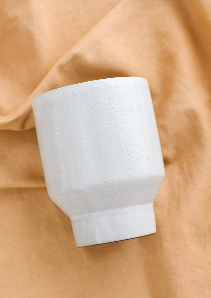 2: A white ceramic cup with a tapered base on brown fabric.