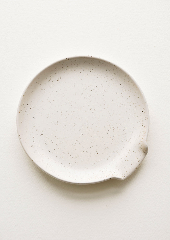 Natural: Circular ceramic spoon rest in ivory with tiny black speckles