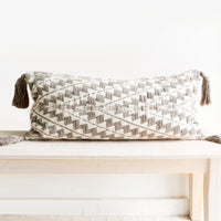1: Long, rectangular pillow in natural cotton with allover geometric chevron embroidery and oversized tassels at corners