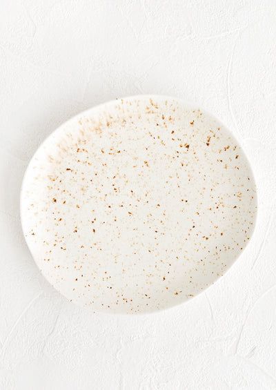 A ceramic plate in white with brown flecks in an organic, subtly asymmetrical round shape.