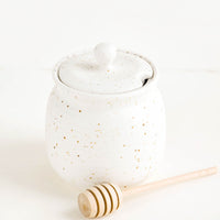 2: Round ceramic honey jar in speckled white glaze with lid and wooden dipper