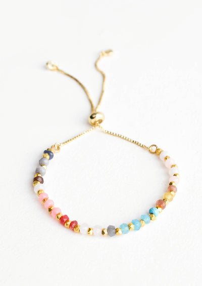 Beaded bracelet in a spectral array of colored gemstone beads, strung on gold chain