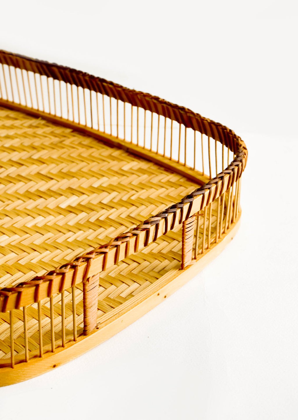 2: Woven tray with spoked rim and cutout handles at ends, made of natural bamboo