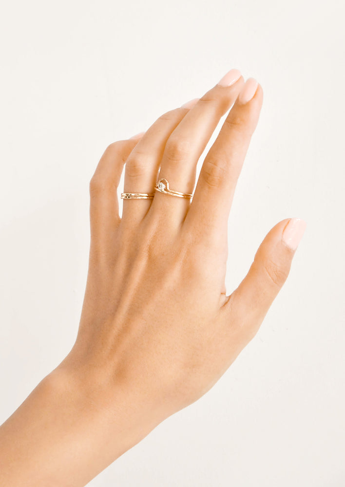 2: Woman's hand with rings on her ring and middle fingers.