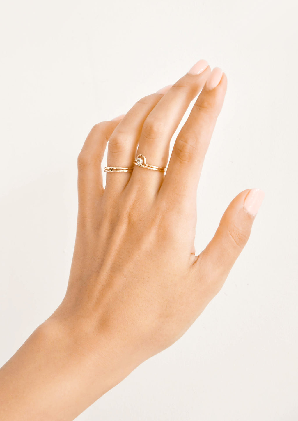 2: Woman's hand with gold rings on her ring and middle fingers.