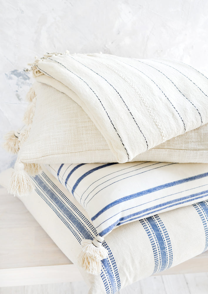 2: A stack of pillows and blankets in blue, white and cream colors.