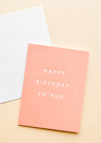 "A white envelope and a coral colored greeting card with the phrase ""happy birthday to you"" in gold black letters."