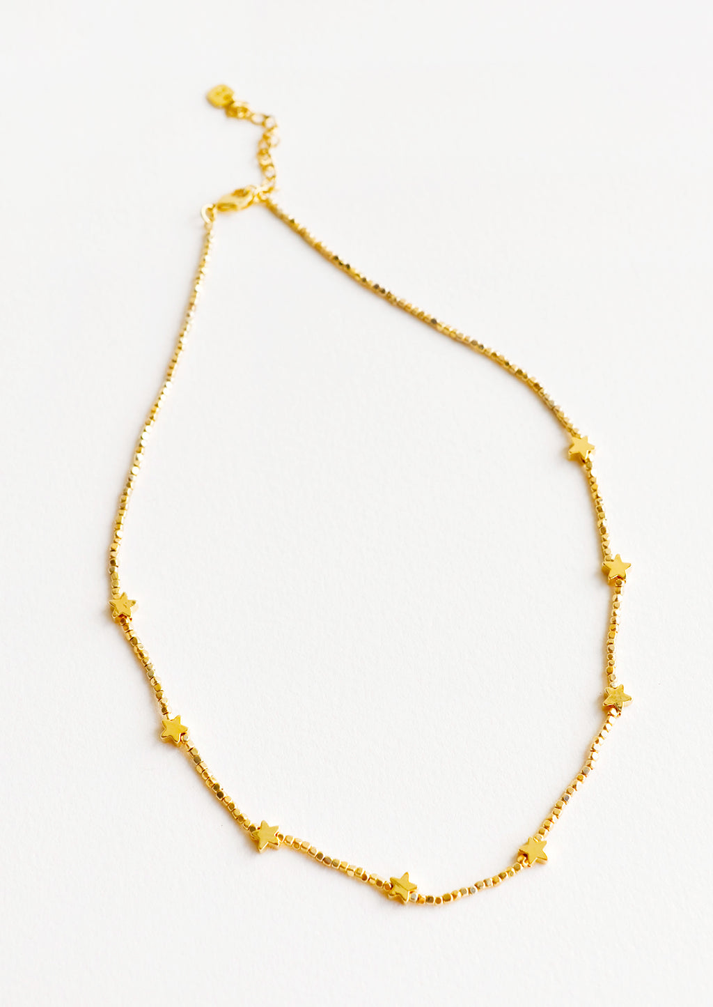 1: Short necklace featuring round yellow gold beads interspersed with gold star beads and an adjustable closure.