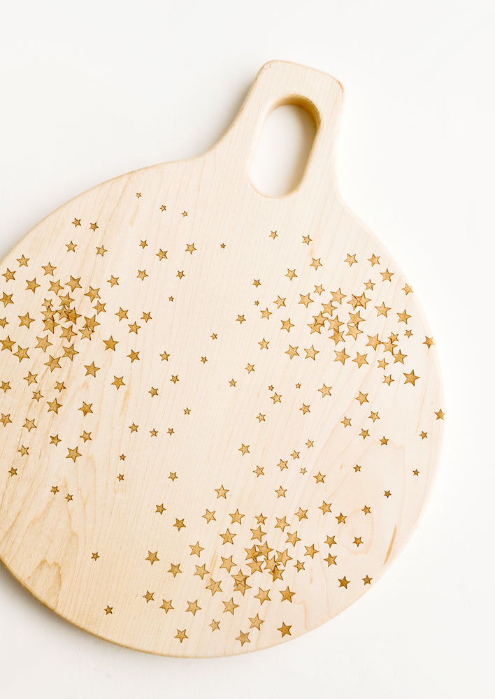 1: Round paddle-style cutting board in maple wood with scattered star pattern