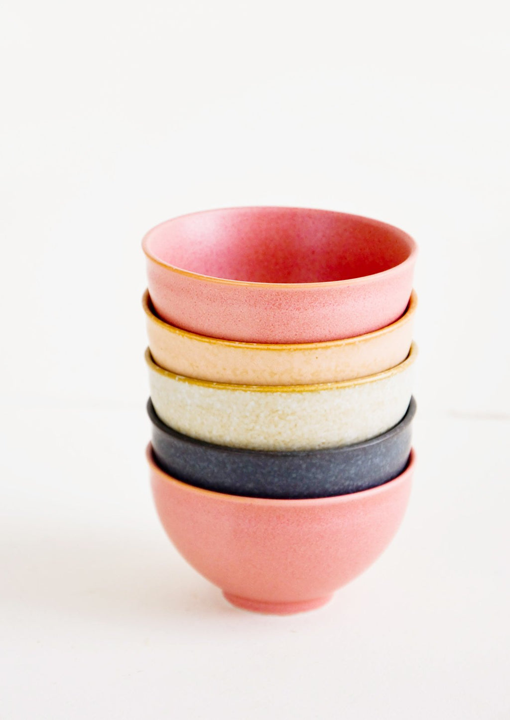 2: Stacked tower of small ceramic bowls in pink, peach, grey and black colors