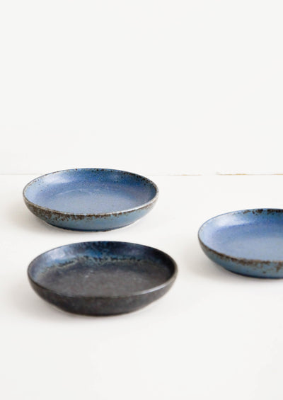 Small, round ceramic plates in a rustic matte glaze in blue and black