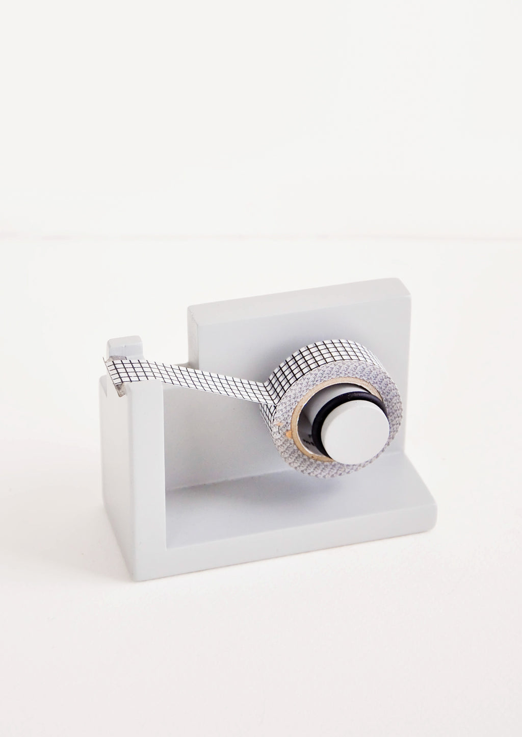 Fog: Gray wooden tape dispenser with black and white tape.