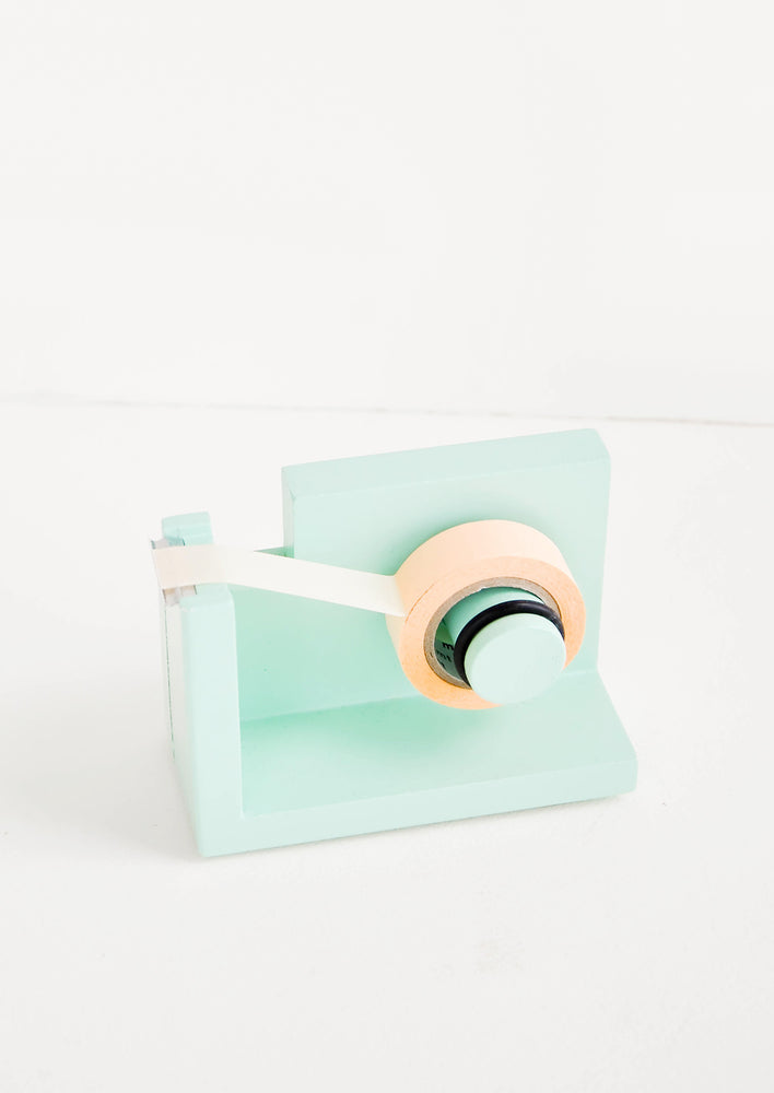 Mint: Green wooden tape dispenser with pink tape.