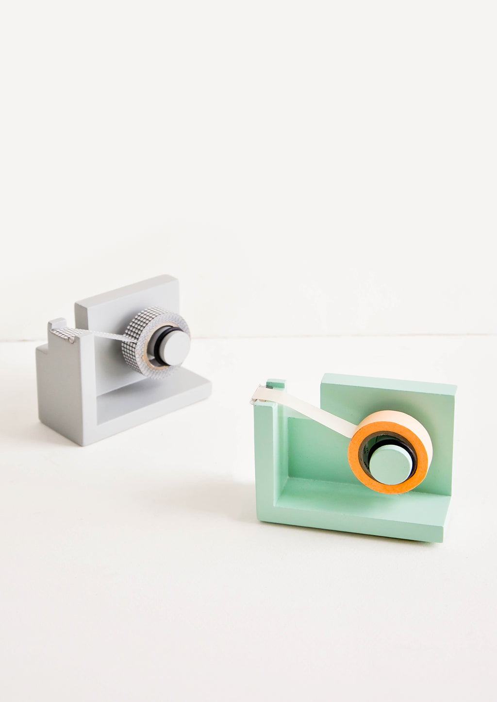 1: Two painted wooden tape dispensers, one gray, one green.
