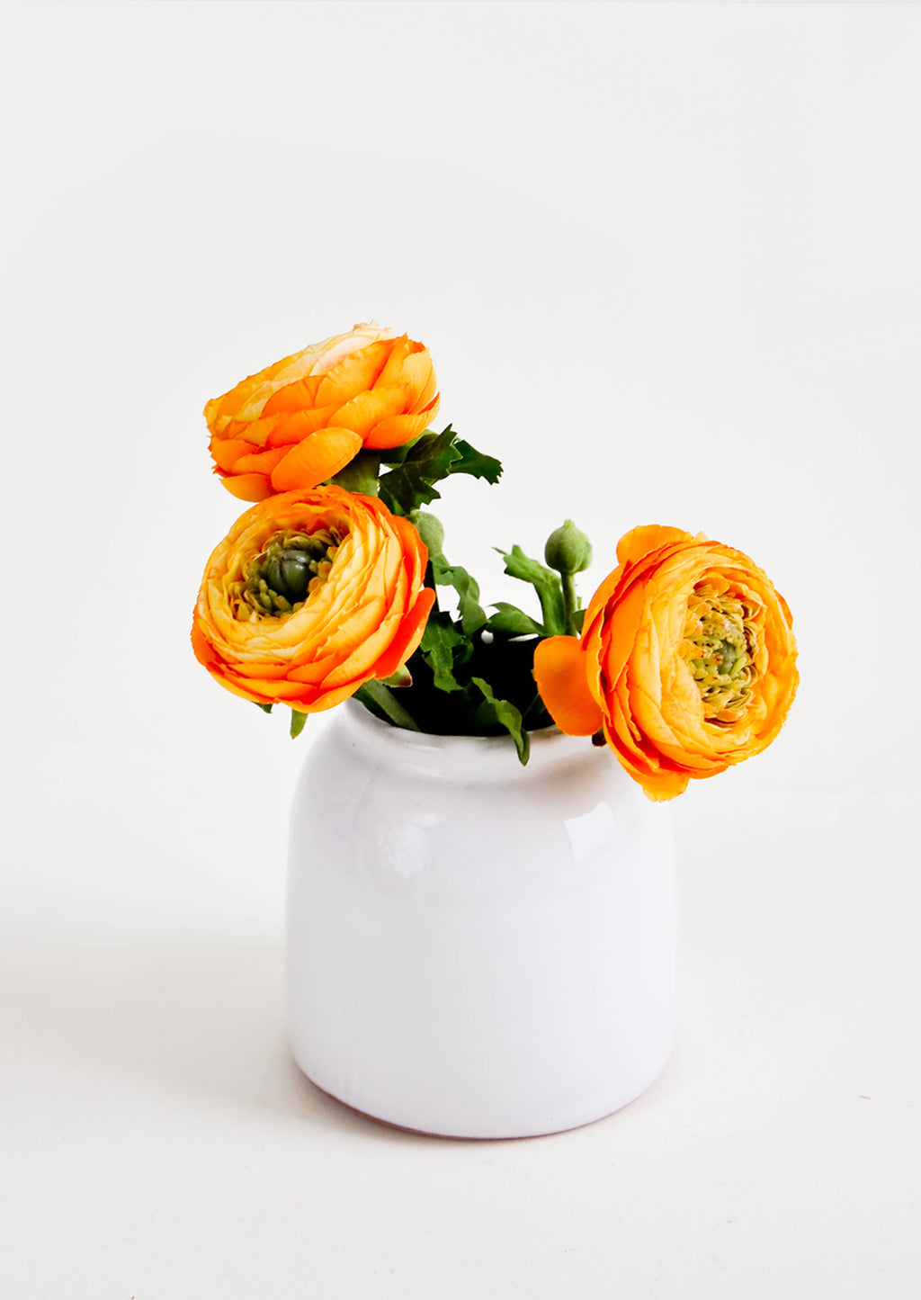 Large / White: Round, white, rustic ceramic vase in glossy finish, pictured with orange flowers