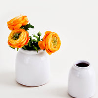 2: Round, white, rustic ceramic vases in glossy finish, pictured with orange flowers