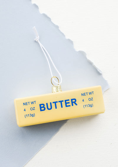 A holiday ornament designed to look like a realistic stick of butter in its paper wrapper.
