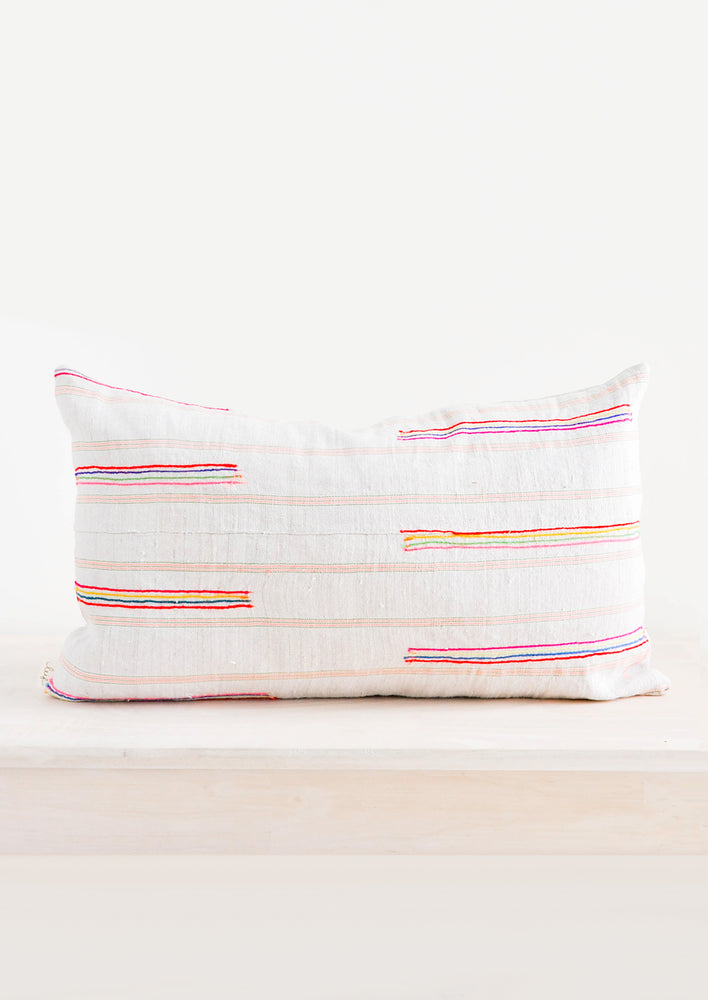 Rectangular throw pillow in light fabric with colorful embroidered lines throughout