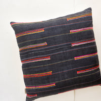 1: Square throw pillow in dark fabric with colorful embroidered lines throughout