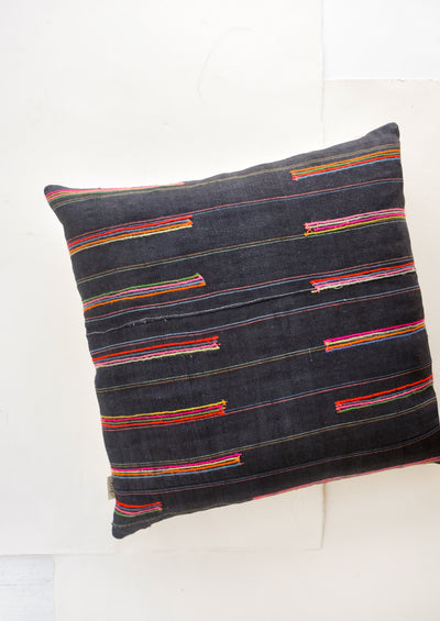 Square throw pillow in dark fabric with colorful embroidered lines throughout