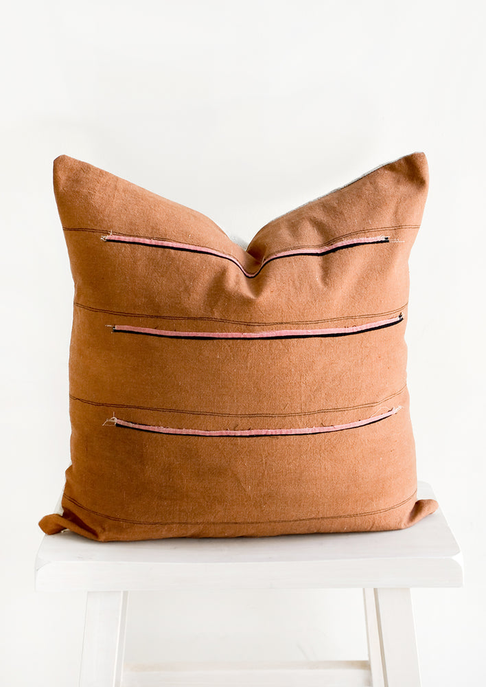 2: Throw pillow in reddish brown fabric with thin black stripes and sewn-on pink and black stripes