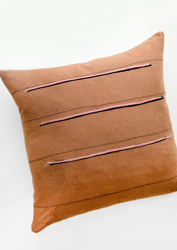 1: Throw pillow in reddish brown fabric with thin black stripes and sewn-on pink and black stripes