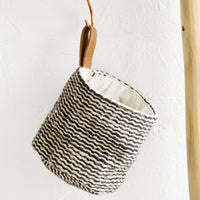 1: A black and white striped jute hanging basket with faux leather strap.
