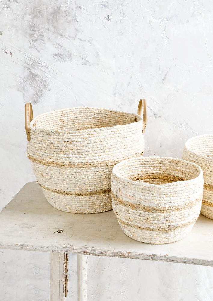 1: Round woven storage baskets in natural color, shown in three incremental sizes