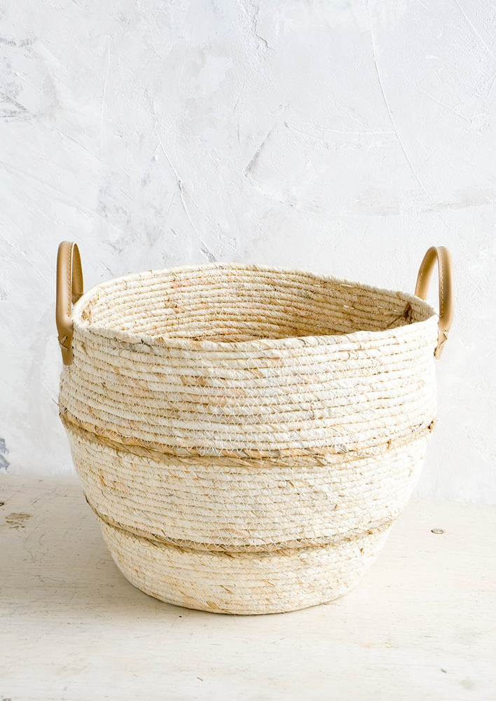 Large [$70.00]: Round storage basket woven from natural maize fiber with tan stripes and leather handles at sides