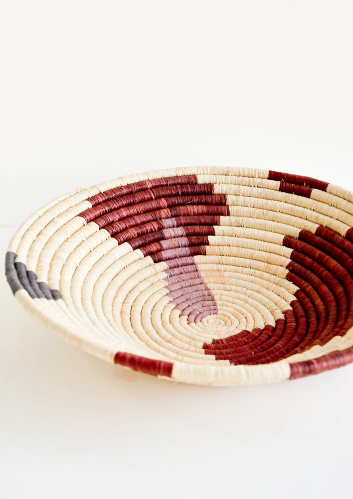 Shallow woven raffia bowl with abstract pattern in lavender, wine and charcoal