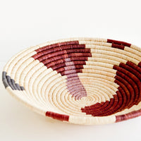 1: Shallow woven raffia bowl with abstract pattern in lavender, wine and charcoal