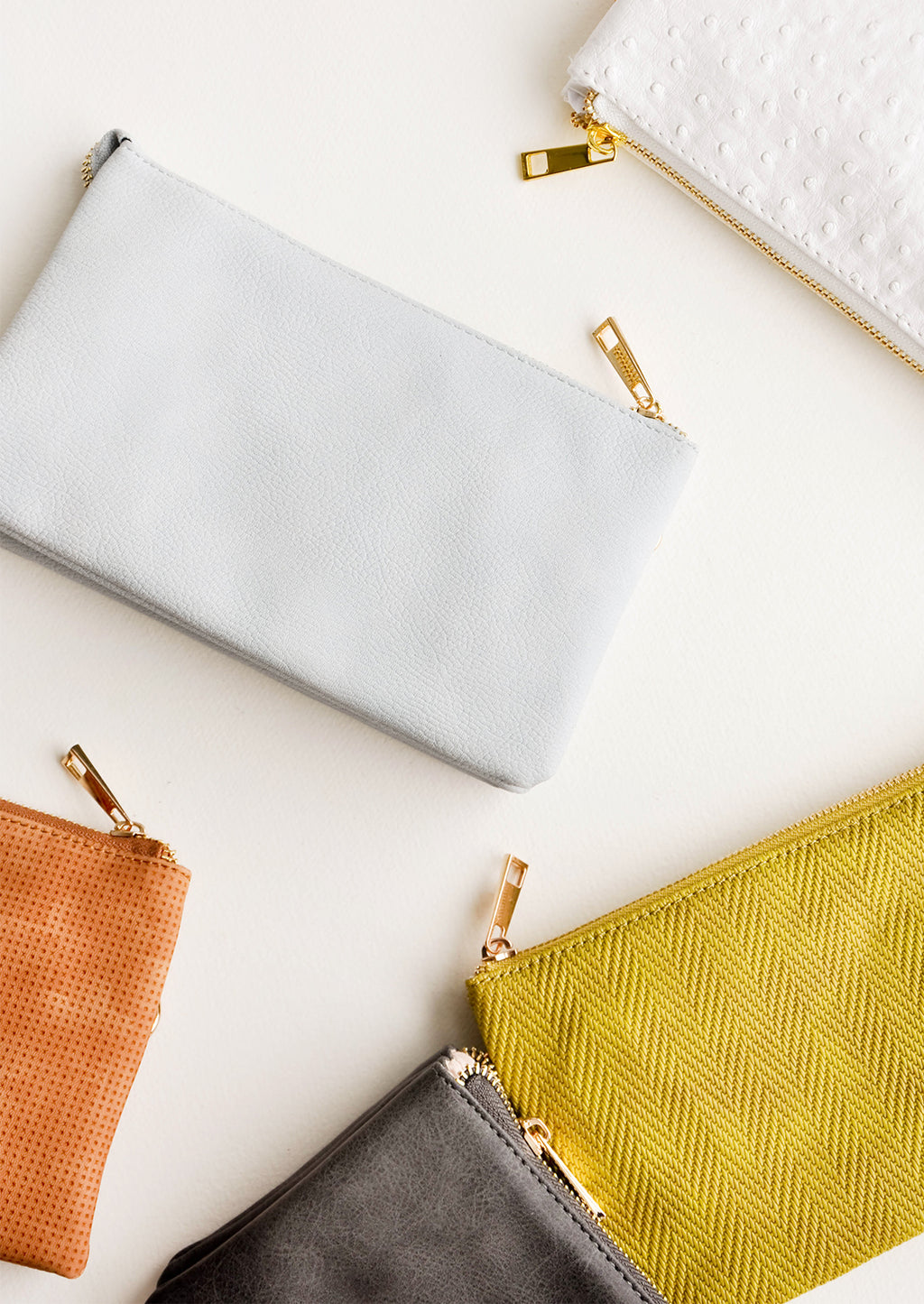 2: Product shot featuring several colors of a clutch purse.