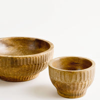 2: Wooden bowls in incremental sizes with footed silhouette and carved detailing on exterior