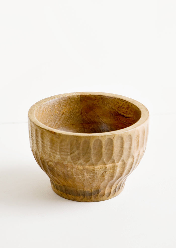 Small: Round mango wood bowl with footed silhouette and carved detailing on exterior