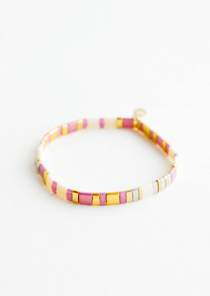 Lavender Cream: Bracelet featuring flat multicolor purple and cream glass beads interspersed with flat gold bead on an elastic cord.