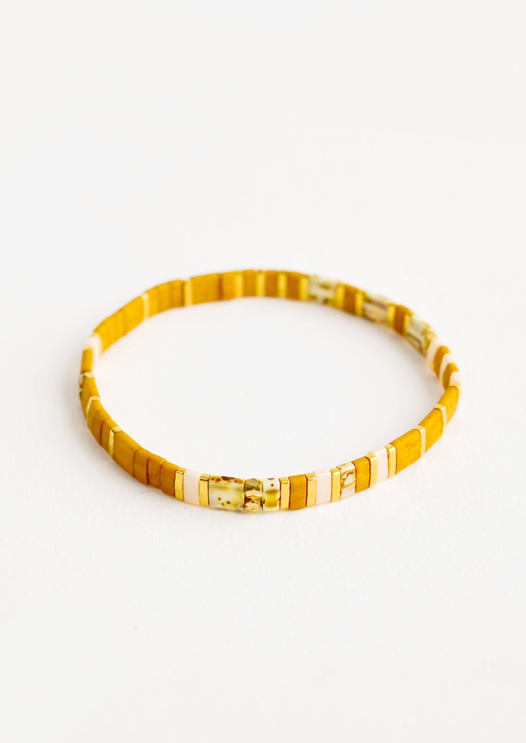 Mustard / Shell Multi: Bracelet featuring flat mustard beads interspersed with flat gold bead on an elastic cord.