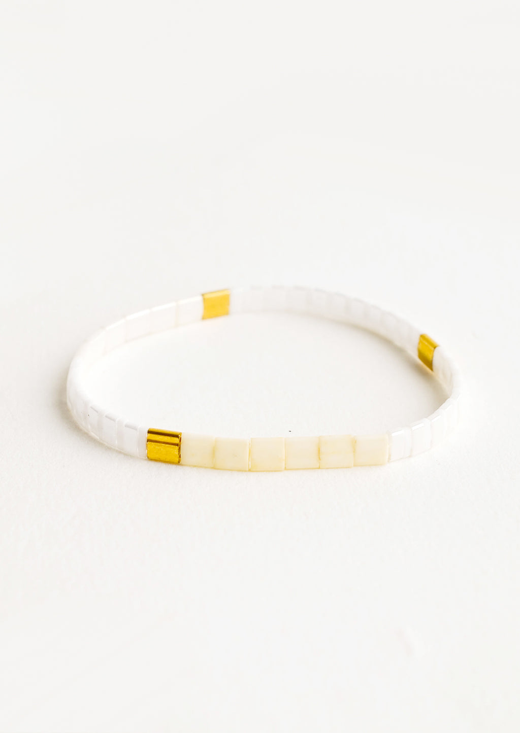 Pearl / Nude Multi: Bracelet featuring flat white beads interspersed with flat gold bead on an elastic cord.