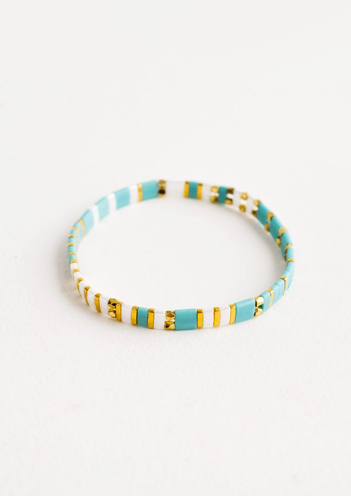 Turquoise / White Multi: Bracelet featuring flat turquoise beads interspersed with flat gold bead on an elastic cord.